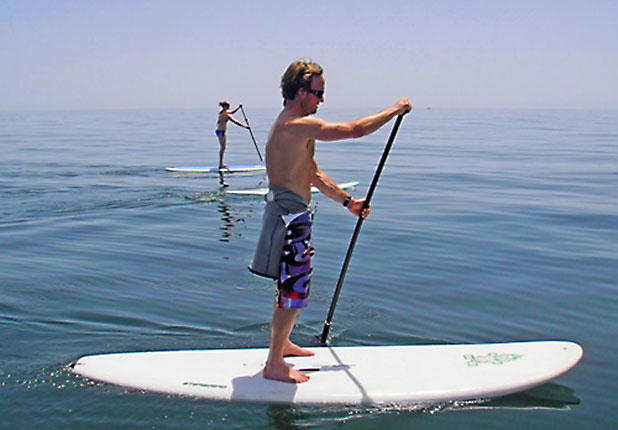 Stand Up Paddle has a larger than average surf board and a long paddle to steer and propel you - photo courtesy of www.standuppaddlemarbella.com