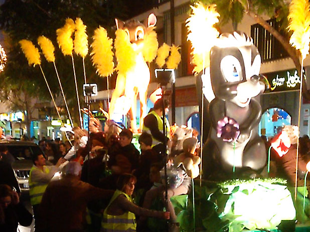 Themed floats slowly pass by with local children throwing sweets into the crowd