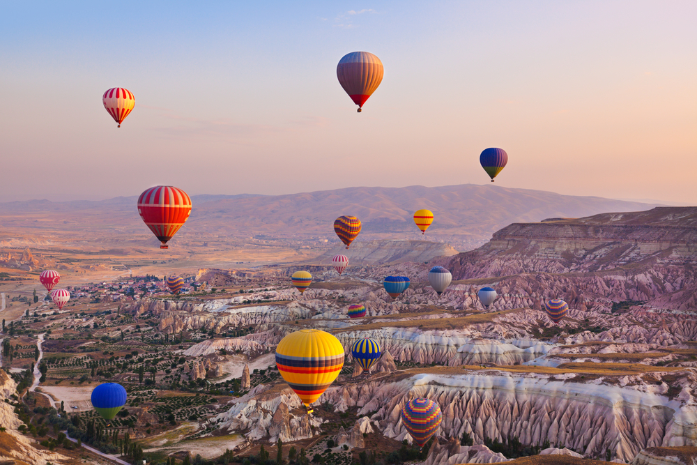 Hot air balloons flying above the volcanic valleys of Cappadocia