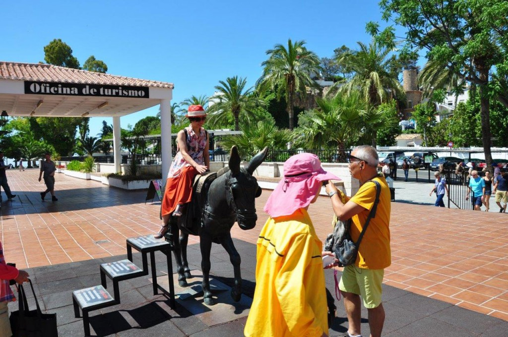 A holidaymaker posing for a photo on the donkey statue